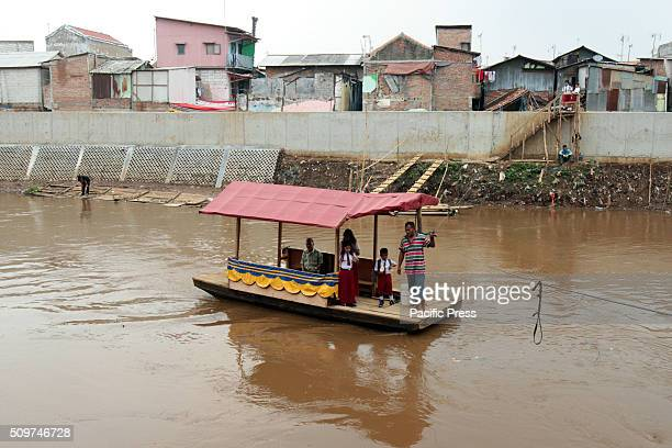 School children ride a boat to cross the Ciliwung River Education in Indonesia still has some obstacles with regard to the access of school and...