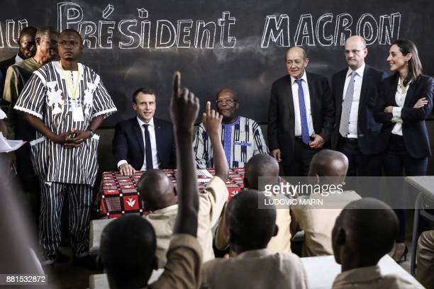 TOPSHOT School children rise their hands as French President Emmanuel Macron and Burkina Faso's President Roch Marc Christian Kabore sit in a...