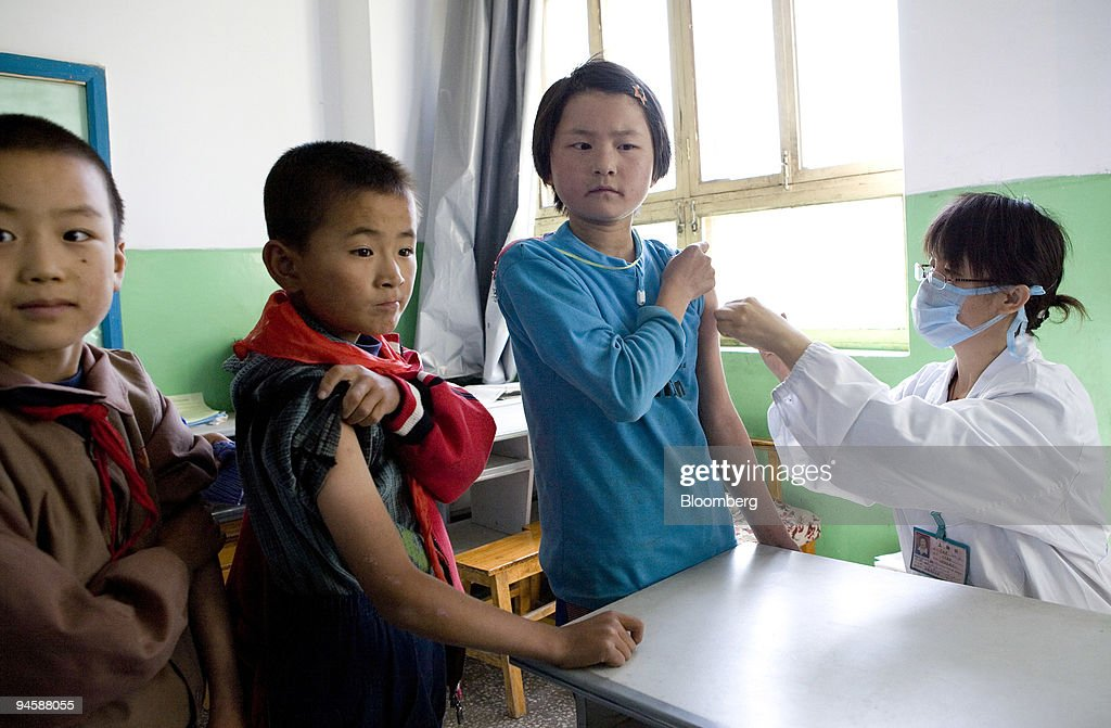 School children roll up their sleeves to receive injections : News Photo