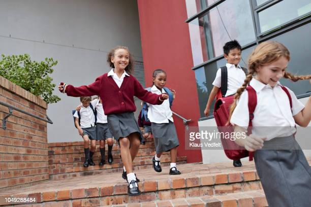 school children running and jumping off staircase from school building - unabhängige schulbildung stock-fotos und bilder
