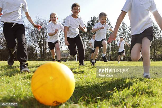School children running for ball in field