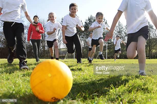 school children running for ball in field