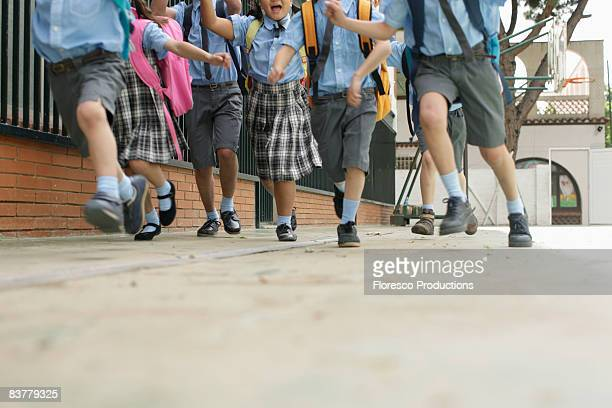 school children running low angle - schuluniform stock-fotos und bilder
