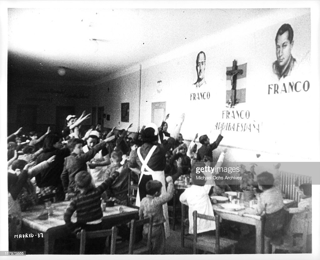 School children salute Franco murals in a scene from the film 'To Die in Madrid' a.k.a. 'Mourir a Madrid', 1965.