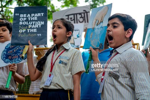 School children shout slogans as they participate in a climate strike to protest against governmental inaction towards climate breakdown and...