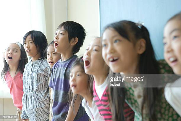 School children (8-9) singing in classroom