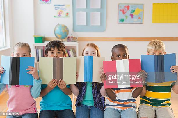 School children (8-9) sitting in row with open books