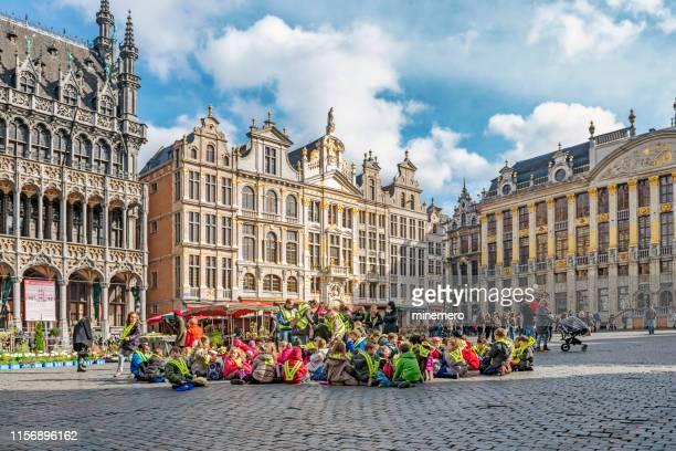 school kinderen zittend op grote markt in brussel - grote markt brussel stockfoto's en -beelden