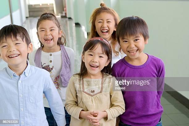 school children (6-9) smiling in corridor - 16:9 ストックフォトと画像