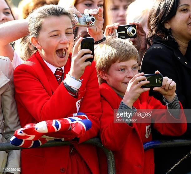 School children take photographs as Queen Elizabeth II arrives in Valentine's Park Redbridge as part of her Diamond Jubilee tour of the UK on March...