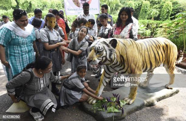 School children tie the rakhi to dummy the Bengal tiger on the occasion of International Tiger Day at Delhi Zoo on July 29 2017 in New Delhi India...
