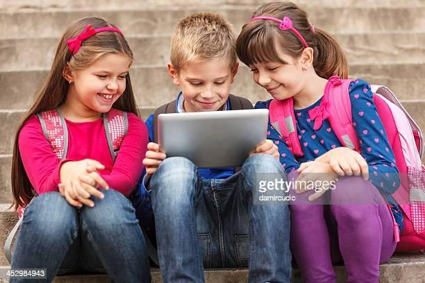Los niños de escuela con tableta digital al