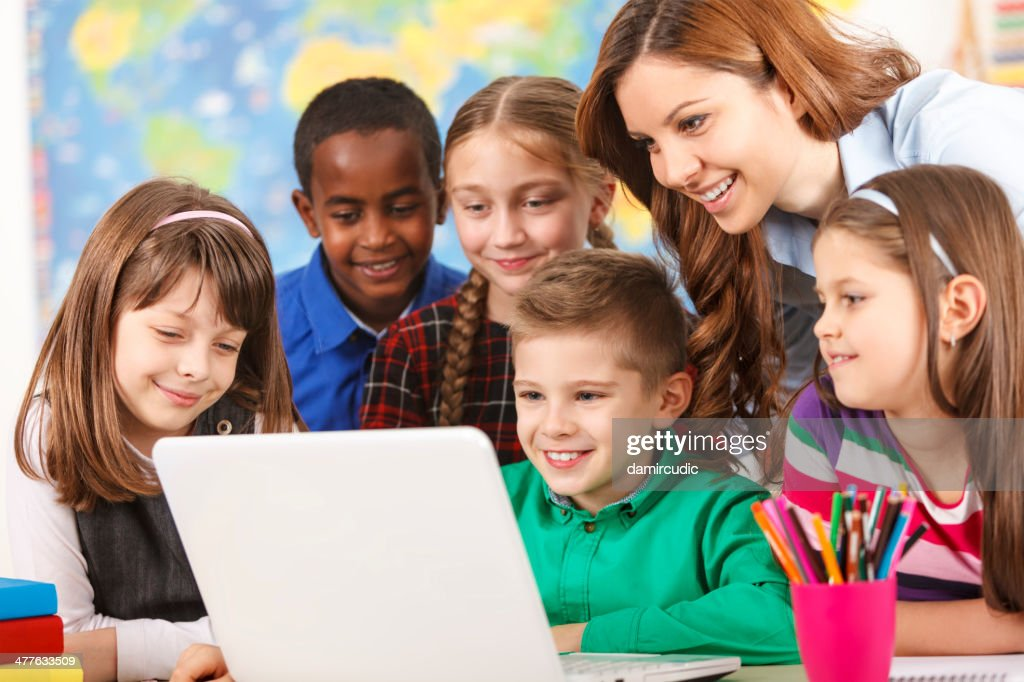 School children using laptop with teacher in the classroom : Stock Photo