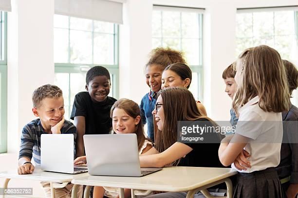 School children usando computadora portátil con el profesor en un aula