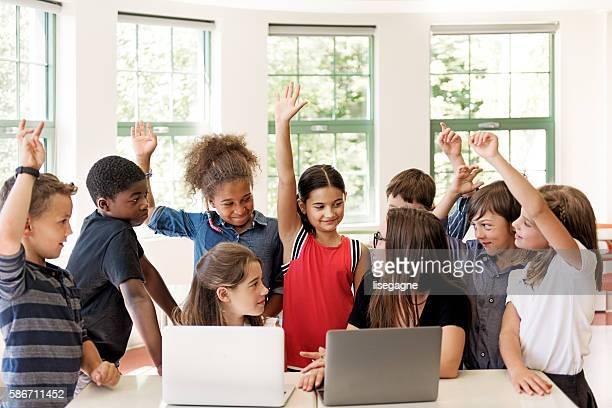 School children using laptop with teacher in the classroom