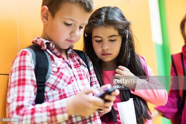 School children using smart phone.