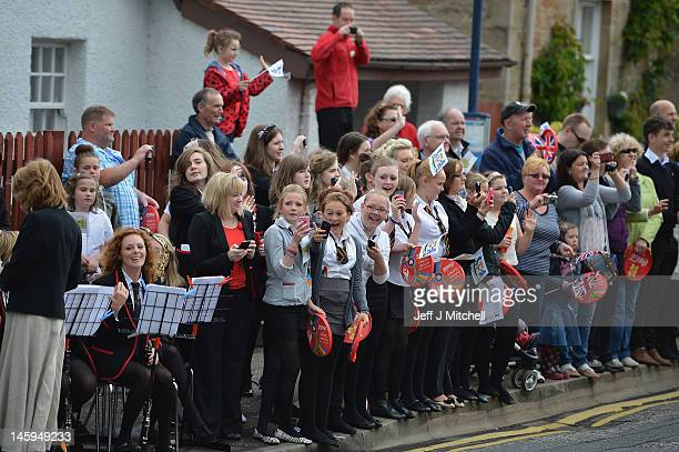 School children wait for the Olympic torch to go past the Robert Burns cottage on the leg between Stranrear and Glasgow on June 8 2012 in Alloway...