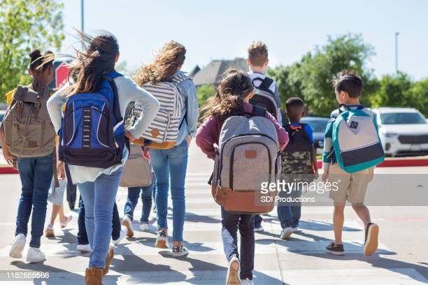 school children walk away from camera in crosswalk - rucksack stock pictures, royalty-free photos & images