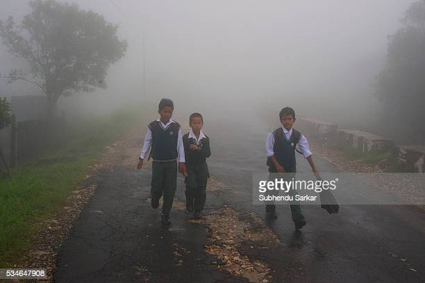 School children walk back home from school along a road in the mist covered Cherapunjee in Meghalaya Cherrapunjee or Charrapunji is a subdivisional...