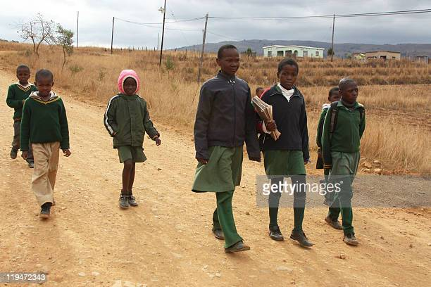 School children walk home near the southern rural village in Sibovu on July 13 2011 More than 100000 children in Swaziland rely on government grants...