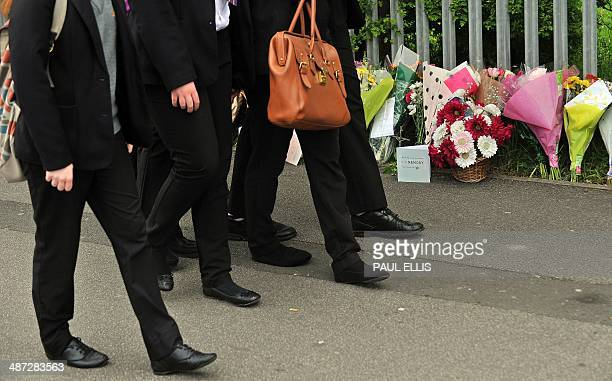 School children walk past floral tributes as they arrive for school at Corpus Christi Catholic College in Leeds northern England on April 29...