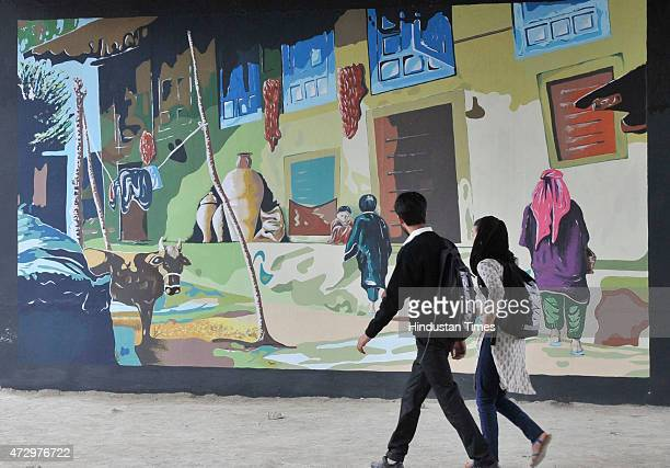 School children walk past the painting murals on the city walls painted by the Fine Arts students from Kashmir University on May 11 2015 in Srinagar...