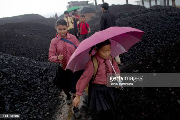 School children walk through a coal depot on their way home from school on April 14 2011 in Lad Rymbai in the district of Jaintia Hills India Local...