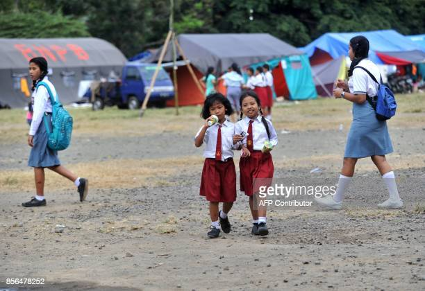 School children walk through a temporary evacuation centre at Ulakan village in the Manggis subdistrict in Karangasem Regency where Mount Agung is...