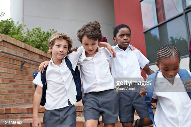 School children walking arm in arm on staircase to school building