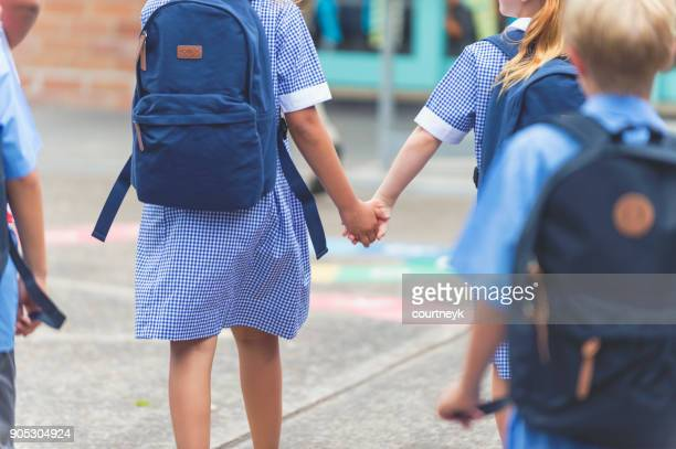 school children walking away. - school building stock pictures, royalty-free photos & images