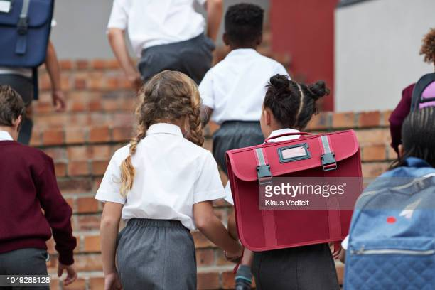 School children walking on staircase to school building