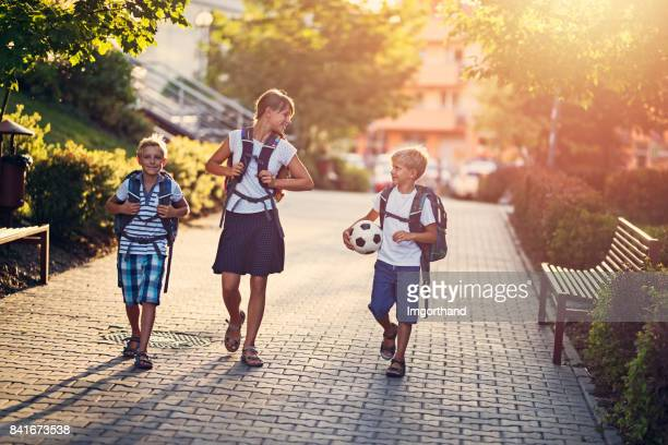 school children walking to school - residential district stock photos and pictures