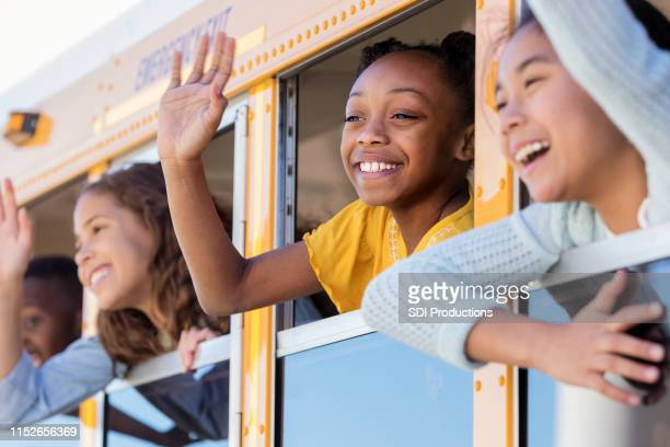 school children wave from school bus - field trip stock pictures, royalty-free photos & images
