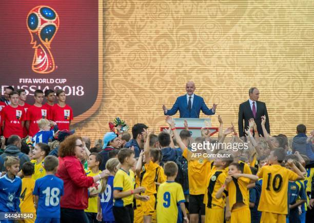 School children wave to the TV cameras while Russian President Vladimir Putin and FIFA President Gianni Infantino attend the ceremony for the opening...