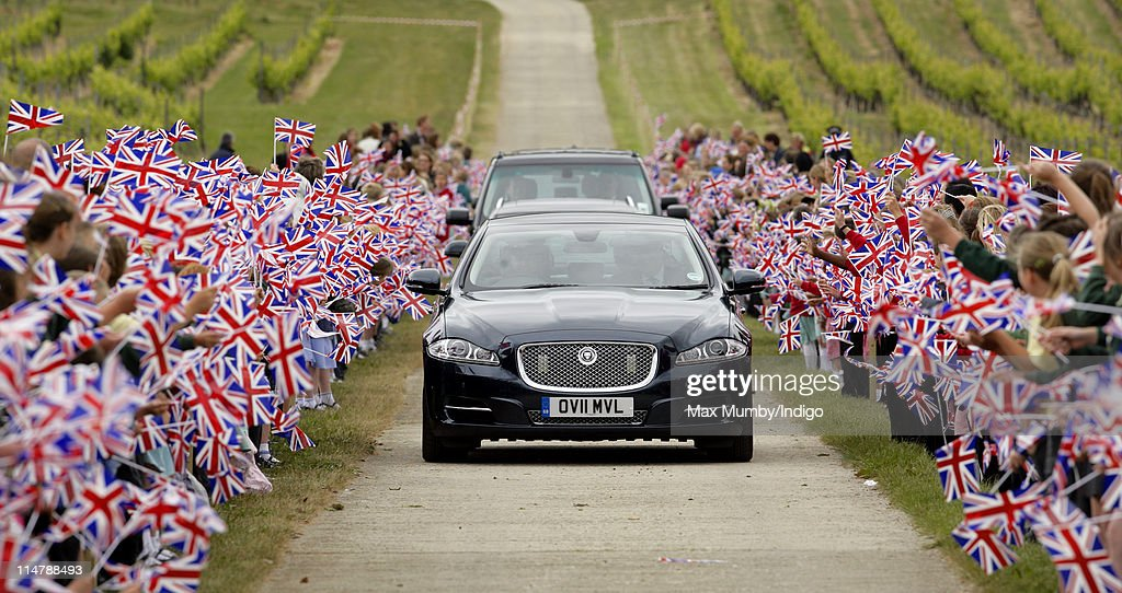 School children wave union flags as Prince Charles' chauffeur driven Jaguar car drives past during a visit to Denbies Wine Estate on May 26, 2011 in Dorking, England.