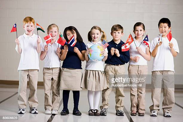 school children waving flags of different countries
