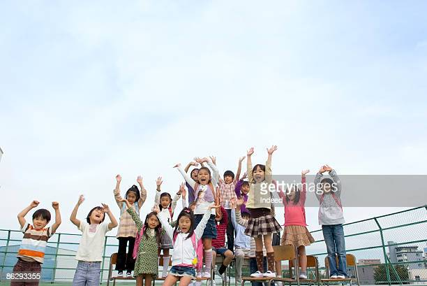 School children (5-11) waving hands