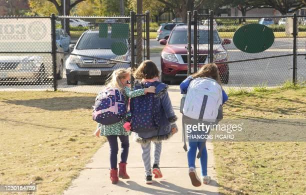 School children wearing facemasks walk outside Condit Elementary School in Bellaire, outside Houston, Texas, on December 16, 2020. - The coronavirus...