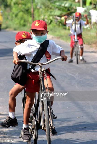 School children wearing masks ride bicycles to school in Blitar near Mount Kelut 22 October 2007 The risk of eruption at an Indonesian volcano on...