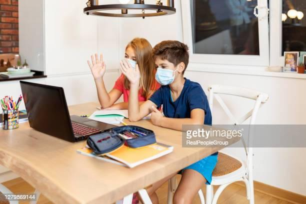 bambini in età scolare che indossano una maschera protettiva per il viso guardando la lezione di educazione online a casa durante l'epidemia di blocco del virus corona - nuovo concetto normale con i bambini felici che si divertono alla riapertura della sc - distante foto e immagini stock