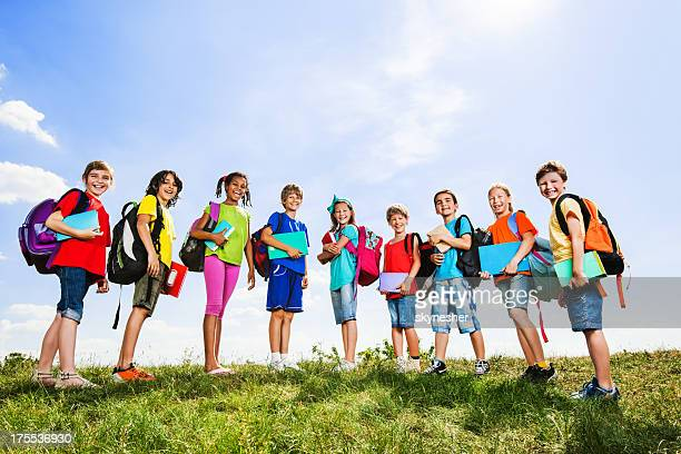 School children with backpacks and books against the sky.