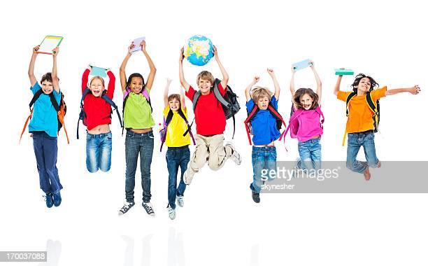 Bambini a scuola con zaini e libri saltare.