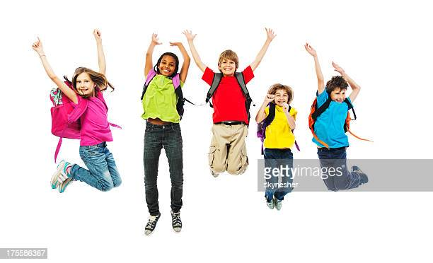 School children with backpacks jumping.
