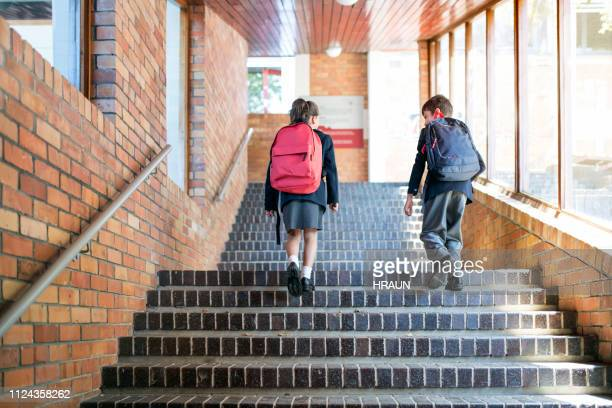 school children with backpacks walking upstairs - education stock pictures, royalty-free photos & images