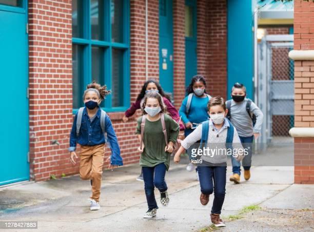 bambini delle scuole con maschere per il viso che corrono fuori dall'edificio - edificio scolastico foto e immagini stock