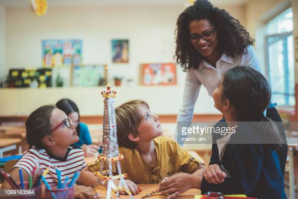 school children with mixed race teacher in class - primary age child stock pictures, royalty-free photos & images