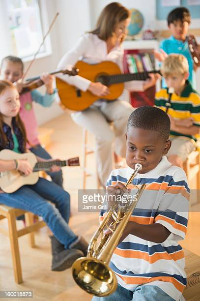 School children (8-9) with teacher playing instruments during music class
