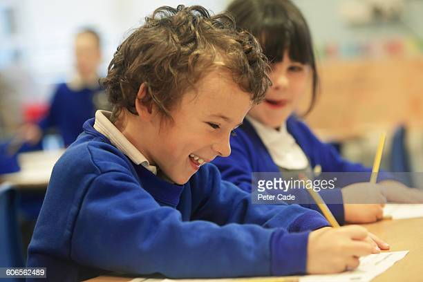 school children writing in class - uniform stock pictures, royalty-free photos & images