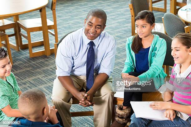 School counselor meeting with diverse group of students after school