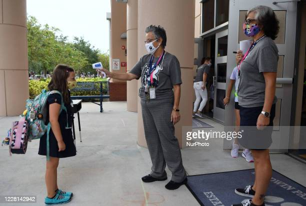 School employee checks the temperature of a student as she returns to school on the first day of in-person classes in Orange County at Baldwin Park...